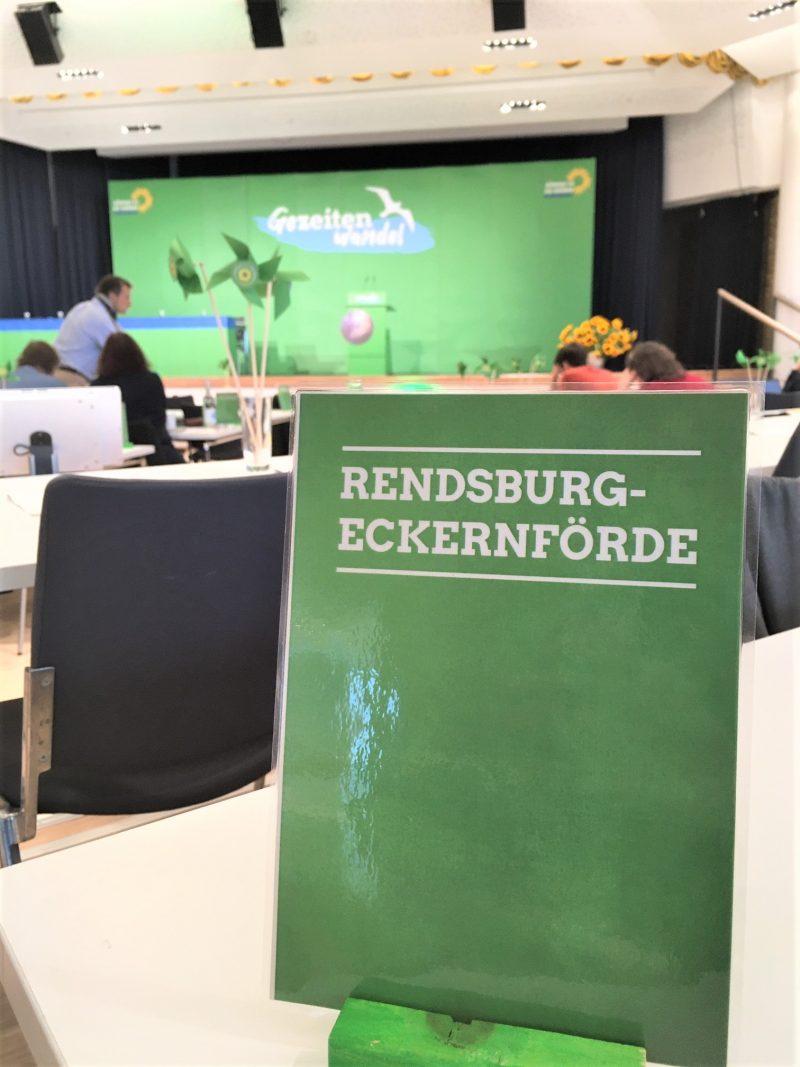 Das Bild zeigt im Vordergrund eine grüne Tischkarte, auf der Rendsburg-Eckernförde geschrieben steht. Der Hintergrund ist unscharf. Man erkennt einen Saal mit Tischen und Stühlen, im Hintergrund ist eine Bühne. Darauf ein Rednerpult. Die Bühne ist leer. Auf einer grünen Wand steht das Motto des Parteitages: Gezeitenwandel.