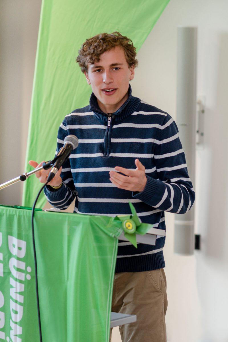 Das Bild zeigt einen jungen Mann mit blonden, lockigen Haaren. Er steht an einem Redepult und spricht. Dabei bewegt er seine Hände auf Brusthöhe. Das Redepult ist mit einer grünen Flagge geschmückt, im Hintergrund ist ebenfalls ein grünes Tuch.